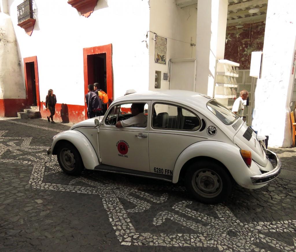 biała taksówka na ulicach Taxco